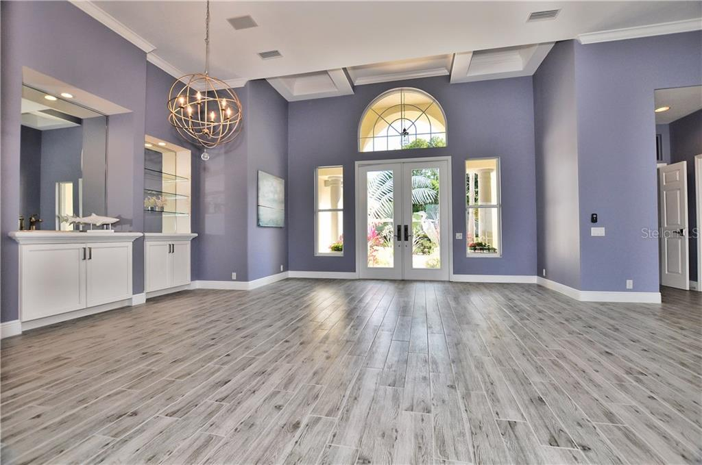 custom made entrance to the front of the house into t he formal living room with a fireplace and mirrored wet bar opens into the large pool lanai. - Single Family Home for sale at 3121 Rivershore Ln, Port Charlotte, FL 33953 - MLS Number is D5917816