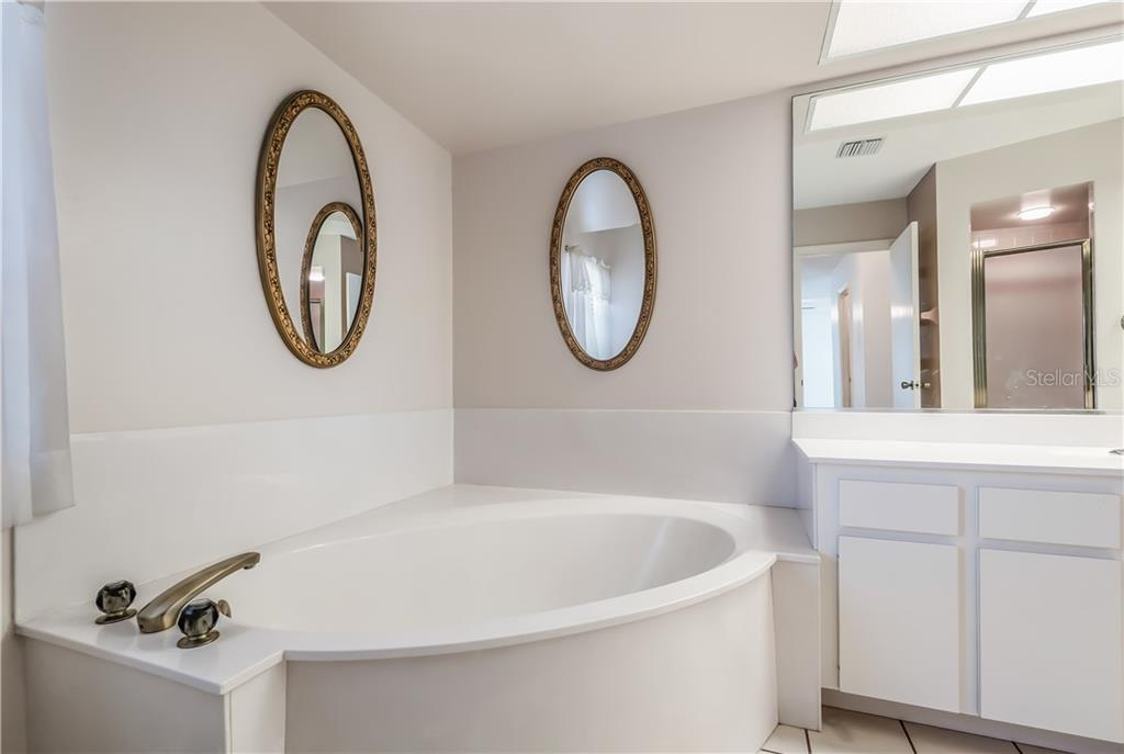 Large master bathroom with deep soaking tub. - Single Family Home for sale at 11010 Deerwood Ave, Englewood, FL 34224 - MLS Number is D5921766