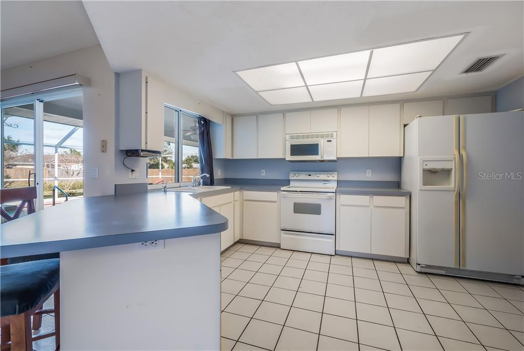 Large open kitchen with breakfast bar and pass through to the pool area. - Single Family Home for sale at 11010 Deerwood Ave, Englewood, FL 34224 - MLS Number is D5921766