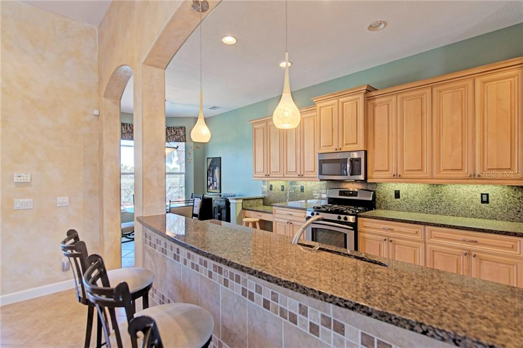 Bar, kitchen and dinette - Single Family Home for sale at 409 Montelluna Drive, North Venice, FL 34275 - MLS Number is D5923522
