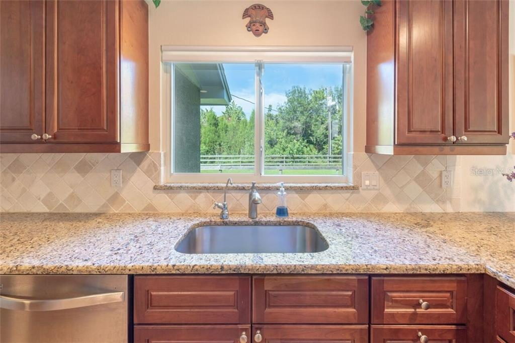 The neighbor is not visible through the greenery at the kitchen window but a deer might be. - Single Family Home for sale at 7339 Hawkins Rd, Sarasota, FL 34241 - MLS Number is D6102762