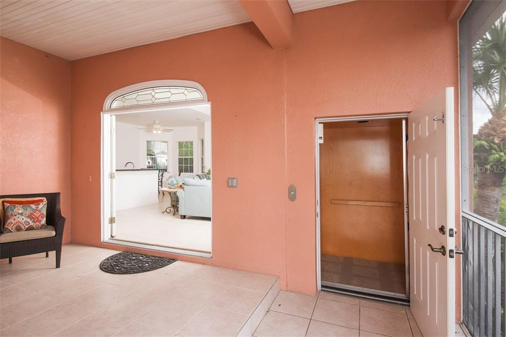 Front entrance with patio and view of the river.  Elevator is door on the right. - Single Family Home for sale at 9033 Allapata Ln, Venice, FL 34293 - MLS Number is D6106356
