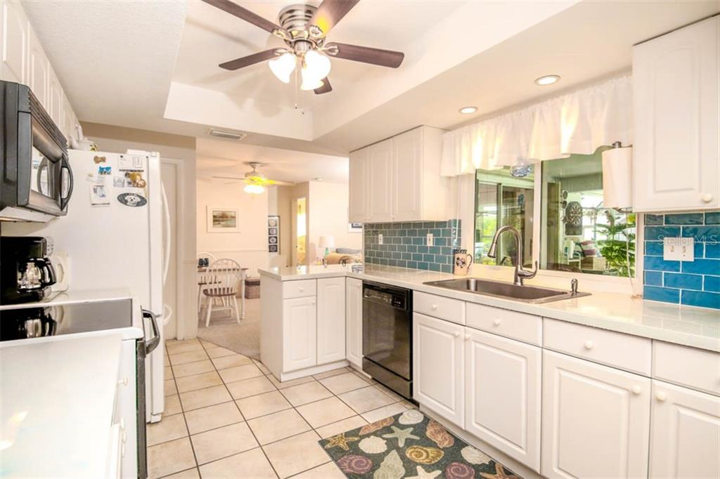 pass thru kitchen window to bar in lanai - Single Family Home for sale at 913 Tropical Ave Nw, Port Charlotte, FL 33948 - MLS Number is D6108061