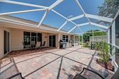 3 sets of sliding glass doors open to the huge lanai with brick paver flooring. - Single Family Home for sale at 7256 Holsum St, Englewood, FL 34224 - MLS Number is D6101787