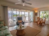 Another view of the living room/dining room combination. Sliders lead out to the balcony with a view of the Intracoastal Waterway and marina. This end unit gives lots of light and beautiful views. - Condo for sale at 7070 Placida Rd #1223, Placida, FL 33946 - MLS Number is D6108523