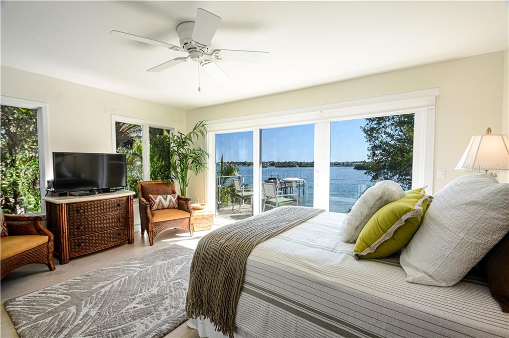 Guest bedroom with access to second floor deck and views to the bay.  Bedroom is en suite with a shower bath - Single Family Home for sale at 140 N Casey Key Rd, Osprey, FL 34229 - MLS Number is T3228618