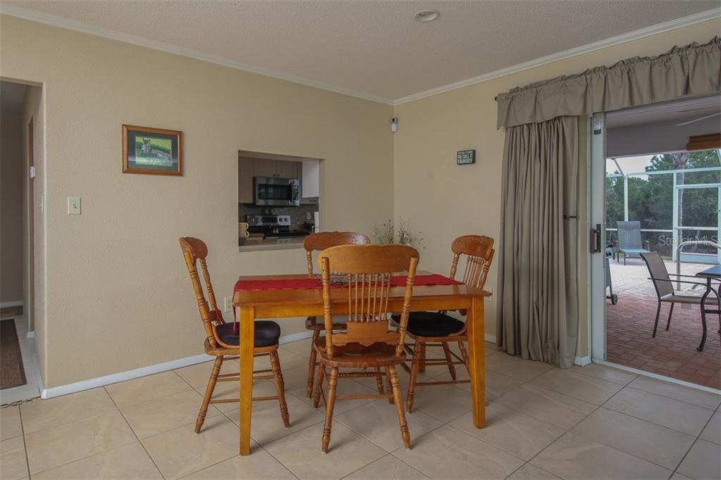 Dining Area in Great Room with pass-thru from Kitchen & Lanai beyond - Single Family Home for sale at 2332 Mauritania Rd, Punta Gorda, FL 33983 - MLS Number is C7234250