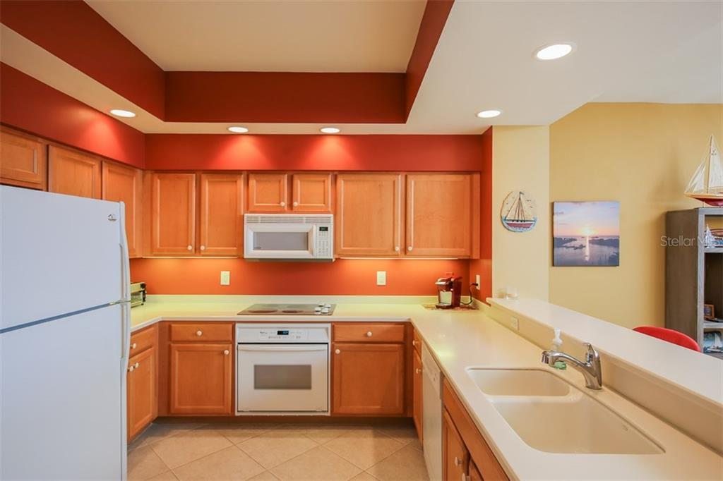 Plentiful cabinetry and work surfaces along with entertaining/breakfast bar completes this well planned kitchen.  Just imagine cooking up today's fresh catch after a nice day on the water. - Condo for sale at 3313 Sunset Key Cir #402, Punta Gorda, FL 33955 - MLS Number is C7236886