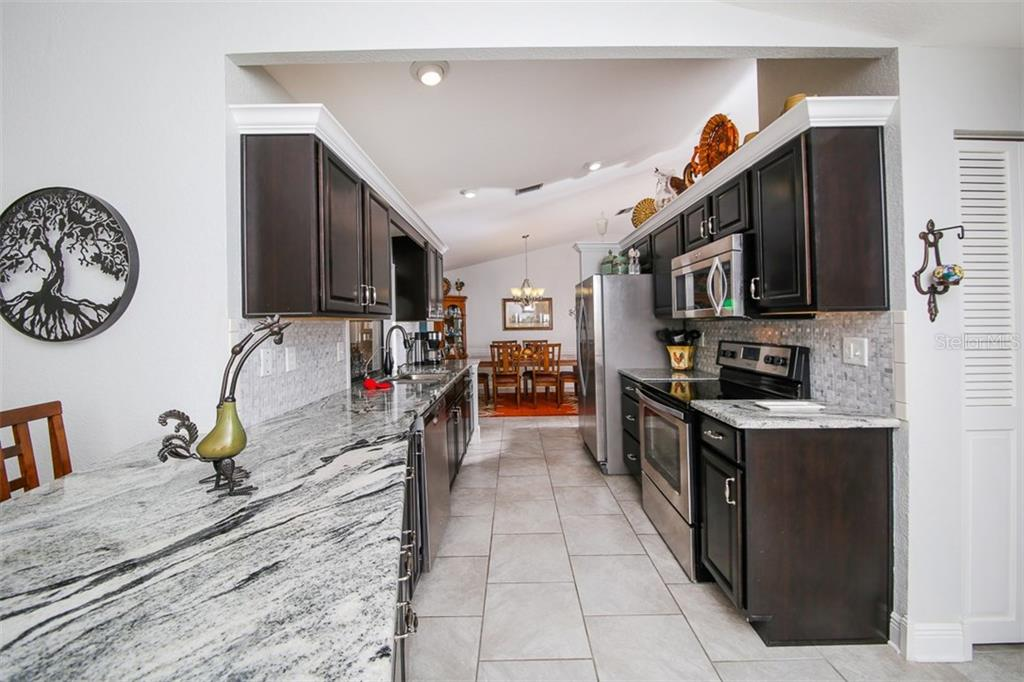 Stunning remodeled kitchen with solid wood cabinets and gorgeous granite counters - please note pictures show cabinets dark - they are actually a rich cappuccino brown color, absolutely beautiful! - Single Family Home for sale at 26178 Rampart Blvd, Punta Gorda, FL 33983 - MLS Number is C7240559