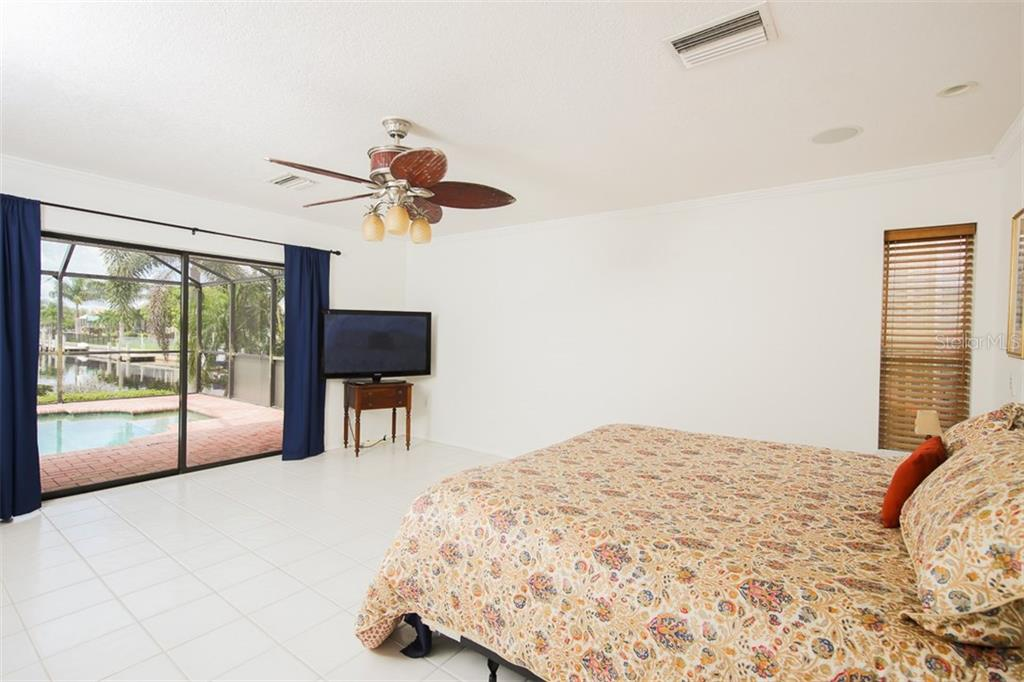Master bedroom with sliders to the inviting tropical outdoors - Single Family Home for sale at 1620 Appian Dr, Punta Gorda, FL 33950 - MLS Number is C7242315