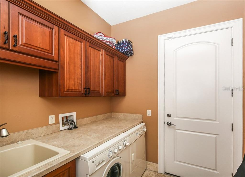 Laundry room boasts companion cherry cabinetry and access to the 4 car garage.  The 4th bay of the garage has it own A/C system and serves as a great spot for storage, hobby area or gym...the choice is yours! - Single Family Home for sale at 17208 Barcrest Ln, Punta Gorda, FL 33955 - MLS Number is C7245458
