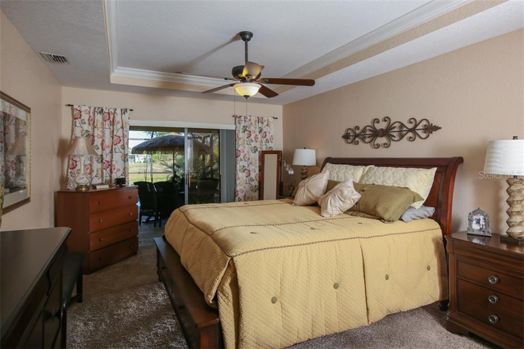 Grand master bedroom has a tray ceiling with crown molding and looks out to the beautiful outdoors - Single Family Home for sale at 220 Broadmoor Ln, Rotonda West, FL 33947 - MLS Number is C7248036