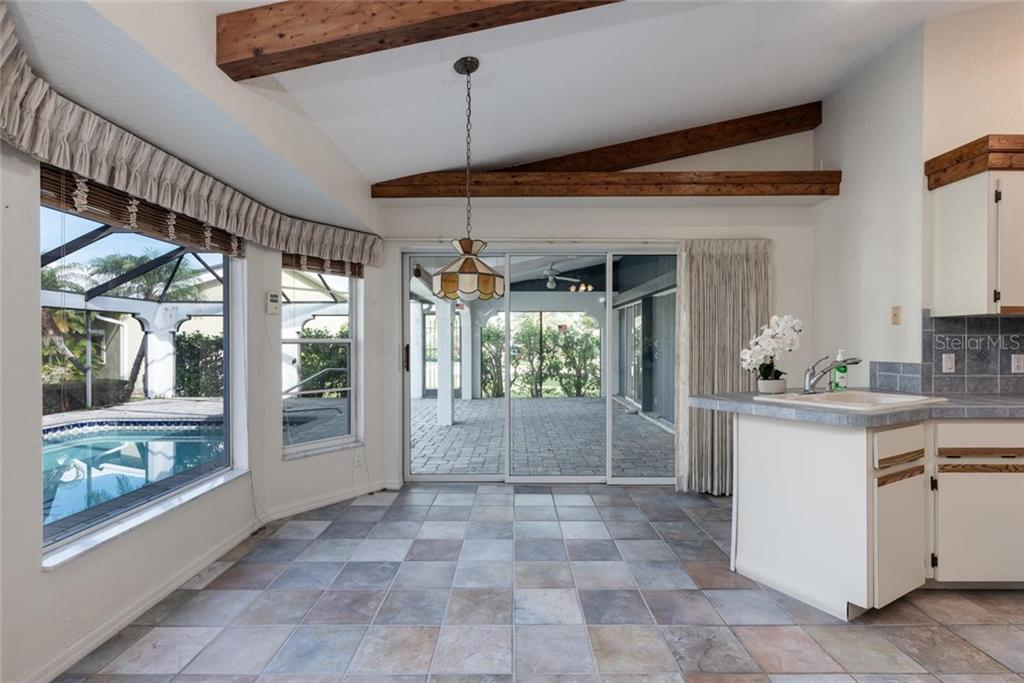 Kichen nook with tile flooring and sliders to lanai.  Beautiful picture window to enjoy the outdoors - Single Family Home for sale at 5001 Captiva Ct, Punta Gorda, FL 33950 - MLS Number is C7422558