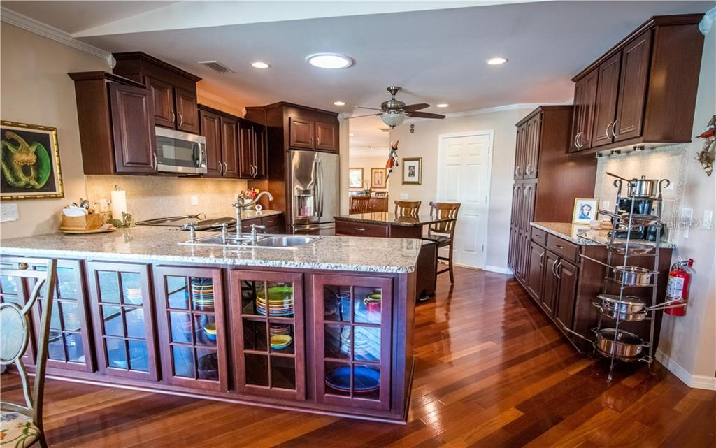 Hardwood cabinets with glass doors provide extra storage in this well-equipped gourmet kitchen. - Single Family Home for sale at 1440 Appian Dr, Punta Gorda, FL 33950 - MLS Number is C7425399