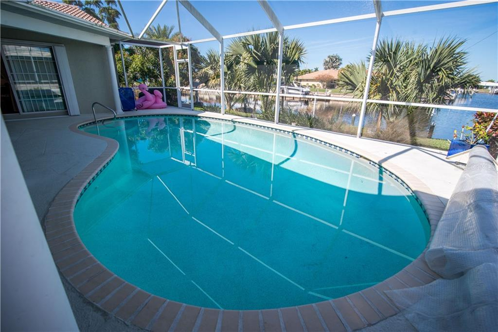 Large heated pool with solar pool cover and exit door to backyard, hammock stands and dock. - Single Family Home for sale at 1440 Appian Dr, Punta Gorda, FL 33950 - MLS Number is C7425399