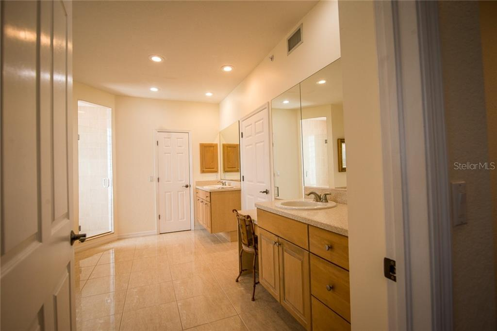 Oversized, the ensuite bath features dual vanities and sinks, walk-in shower, jetted tub and the owners' walk-in custom closet. - Condo for sale at 4410 Warren Ave #511, Port Charlotte, FL 33953 - MLS Number is C7432222