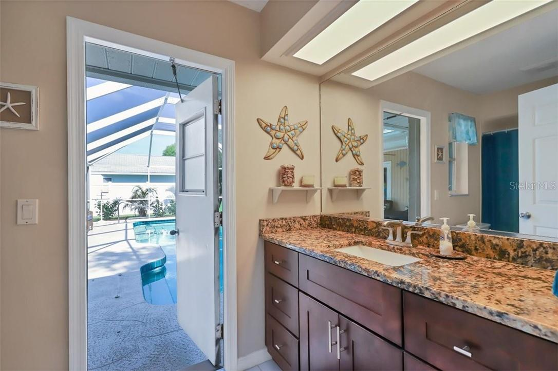 just across hall from bed 2 is the guest bath with updated cabinetry and granite counter tops and newer toilet as well.  Exit door right out to pool and lanai area - no wet feet tracking through the house from swimmers! - Single Family Home for sale at 116 Mariner Ln, Rotonda West, FL 33947 - MLS Number is C7441260
