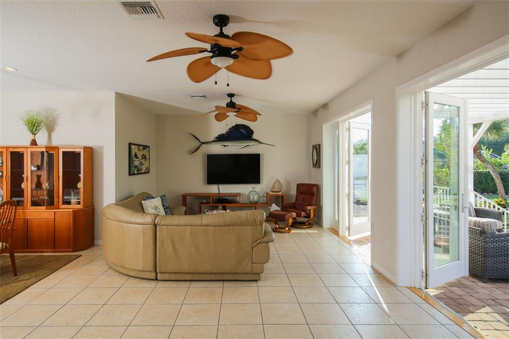 Family room with French doors to paver brick lanai - Single Family Home for sale at 827 Paradise Way, Sarasota, FL 34242 - MLS Number is A4167744