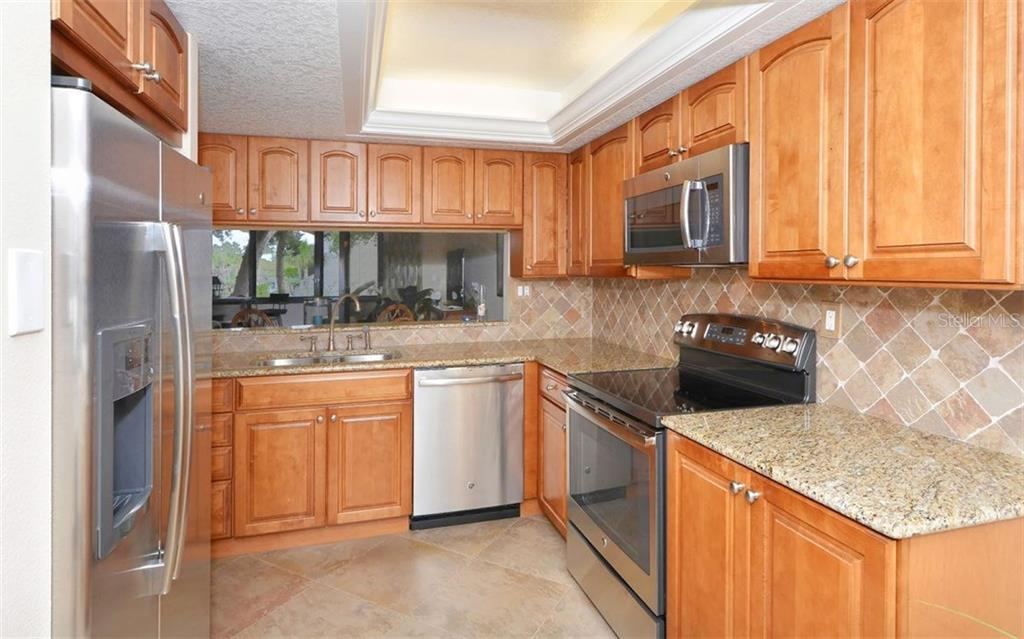 Kitchen with pass-thru to dining area - Condo for sale at 6263 Midnight Pass Rd #101, Sarasota, FL 34242 - MLS Number is A4182245