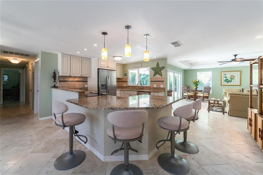 Granite counters grace the fully updated kitchen with a pass thru window to the outdoor dining area. - Single Family Home for sale at 413 Bay Palms Dr, Holmes Beach, FL 34217 - MLS Number is A4184679