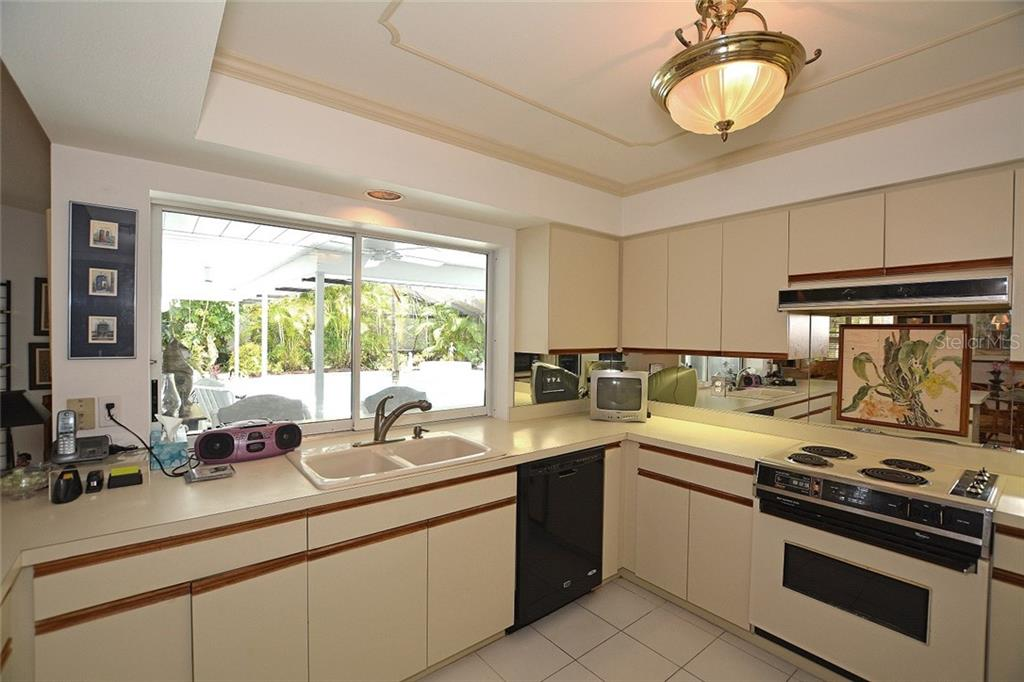 Spacious kitchen with lots of cabinet space for storage and pretty view to the screened lanai and pool area. - Single Family Home for sale at 1157 Wyeth Dr, Nokomis, FL 34275 - MLS Number is A4185839