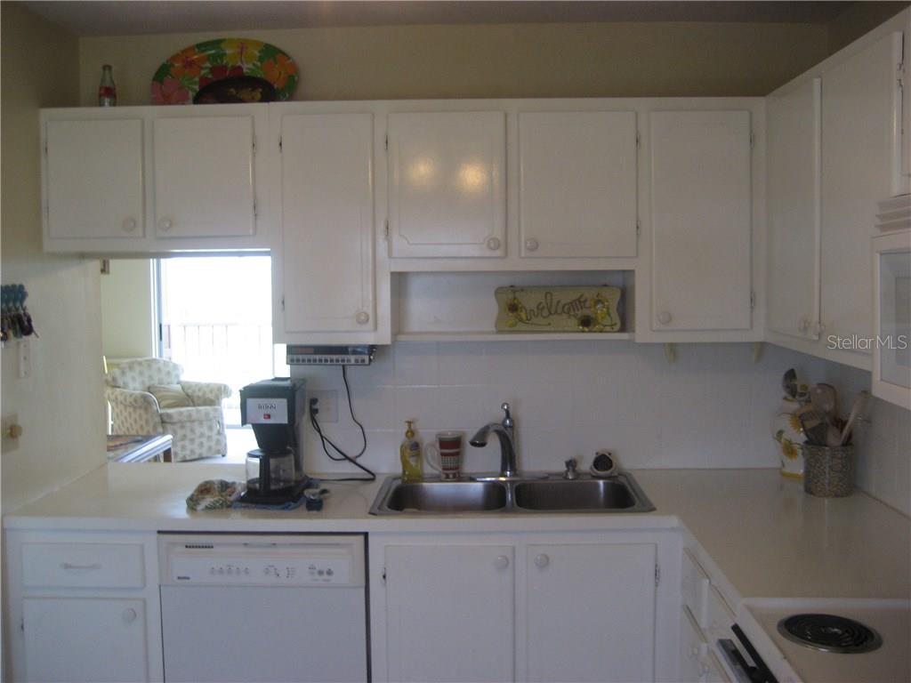 Lots of cabinets for storage and pass through to the dining area - Condo for sale at 3820 Ironwood Ln #606i, Bradenton, FL 34209 - MLS Number is A4187664