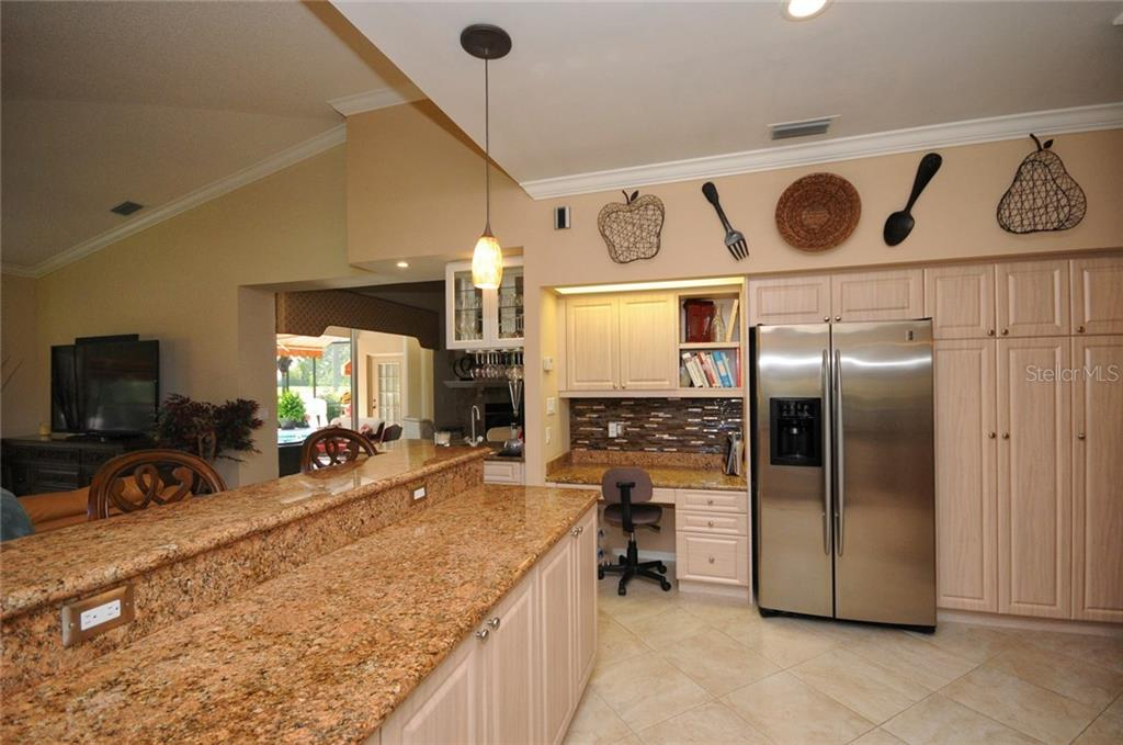 Kitchen with built-in desk - Villa for sale at 7707 Calle Facil, Sarasota, FL 34238 - MLS Number is A4191635
