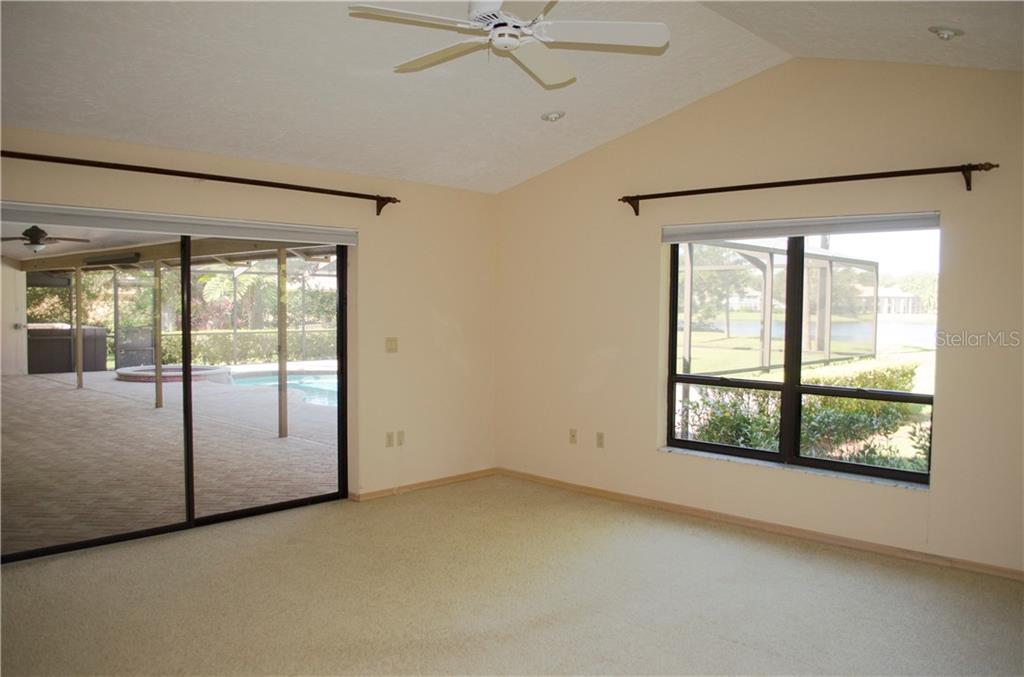 master bedroom overlooks covered patio and view of the lake. also has a vaulted ceiling and has plenty of windows for natural light - Single Family Home for sale at 7529 Weeping Willow Blvd, Sarasota, FL 34241 - MLS Number is A4201676