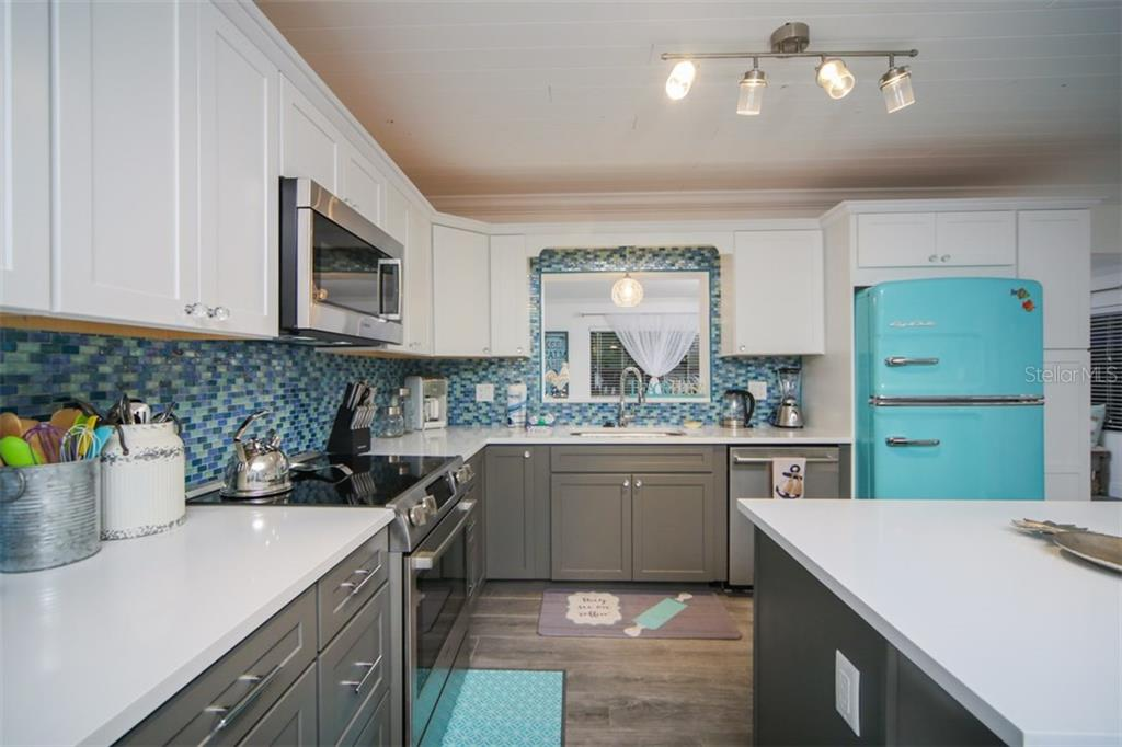 Two tone shaker cabinets with glass backsplash - Single Family Home for sale at 213 70th St, Holmes Beach, FL 34217 - MLS Number is A4202171