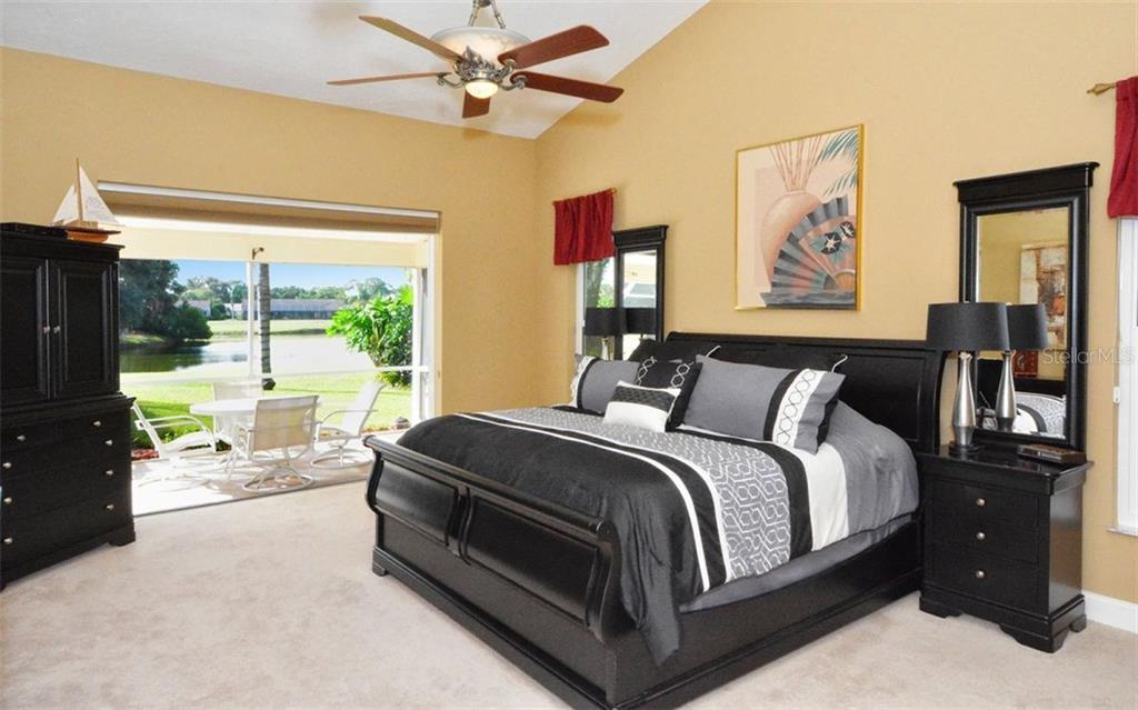 Master bedroom with sliders to sitting area in lanai - over looks lake - Single Family Home for sale at 3882 Spyglass Hill Rd, Sarasota, FL 34238 - MLS Number is A4206477