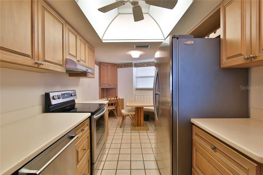 Kitchen with new appliances, built in breakfast nook and corner desk - Condo for sale at 5790 Midnight Pass Rd #704, Sarasota, FL 34242 - MLS Number is A4208095