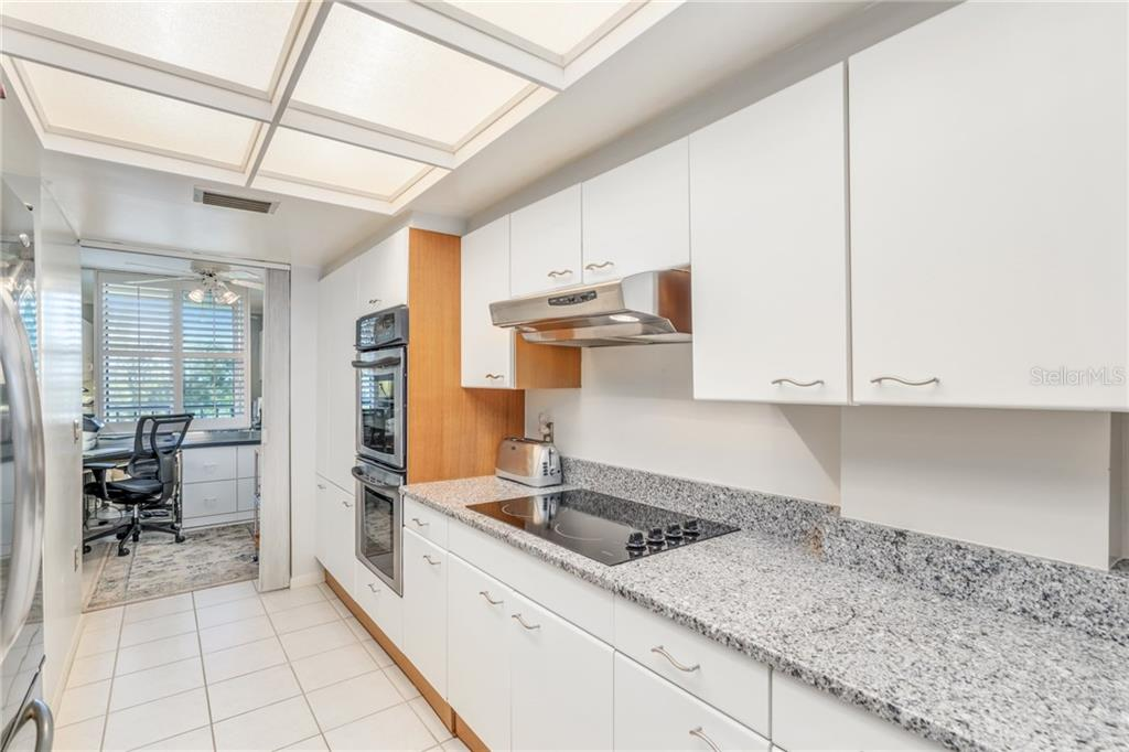 S/S double ovens, french door refrigerator, granite countertops. Office/den in background - Condo for sale at 5880 Midnight Pass Rd #810, Sarasota, FL 34242 - MLS Number is A4208619