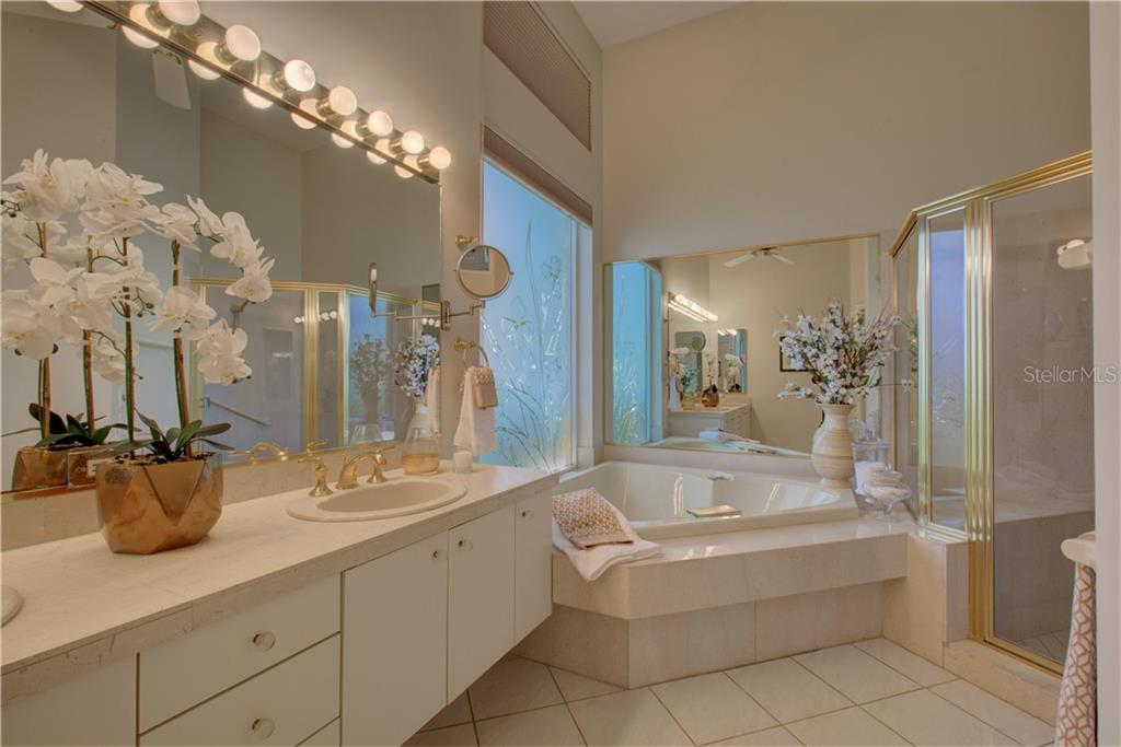 Master bath with dual vanities, spa bath and decorative window. - Single Family Home for sale at 3896 Boca Pointe Dr, Sarasota, FL 34238 - MLS Number is A4213831