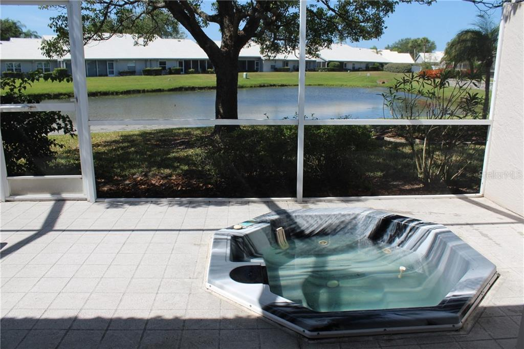 View from covered lanai looking south, past the mature oak tree and large, tranquil pond. - Villa for sale at 5438 Kelly Dr #12, Sarasota, FL 34233 - MLS Number is A4400319