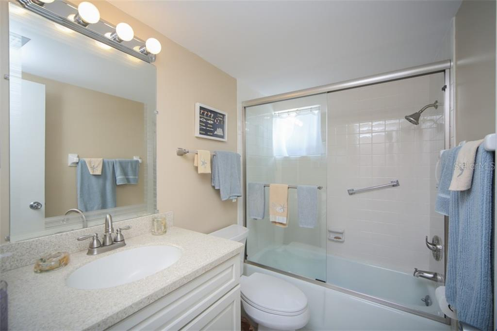 Guest bath has tub and shower, updated elevated toilet, updated vanity. - Condo for sale at 5200 Gulf Dr #101, Holmes Beach, FL 34217 - MLS Number is A4404016