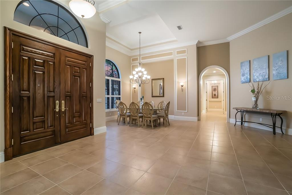 Showcases the stunning double front doors and formal dining. The archway leads to guest bedrooms. - Single Family Home for sale at 13223 Palmers Creek Ter, Lakewood Ranch, FL 34202 - MLS Number is A4408290