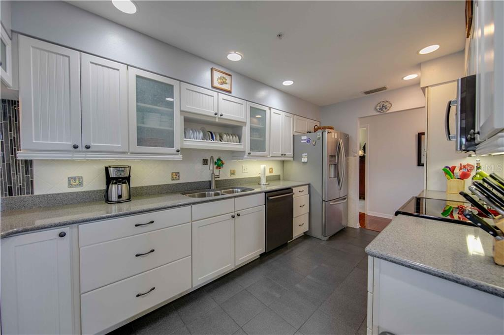 The kitchen features lighted cabinets, solid surface counter tops, and stainless steel appliances - Single Family Home for sale at 660 Marbury Ln, Longboat Key, FL 34228 - MLS Number is A4415911