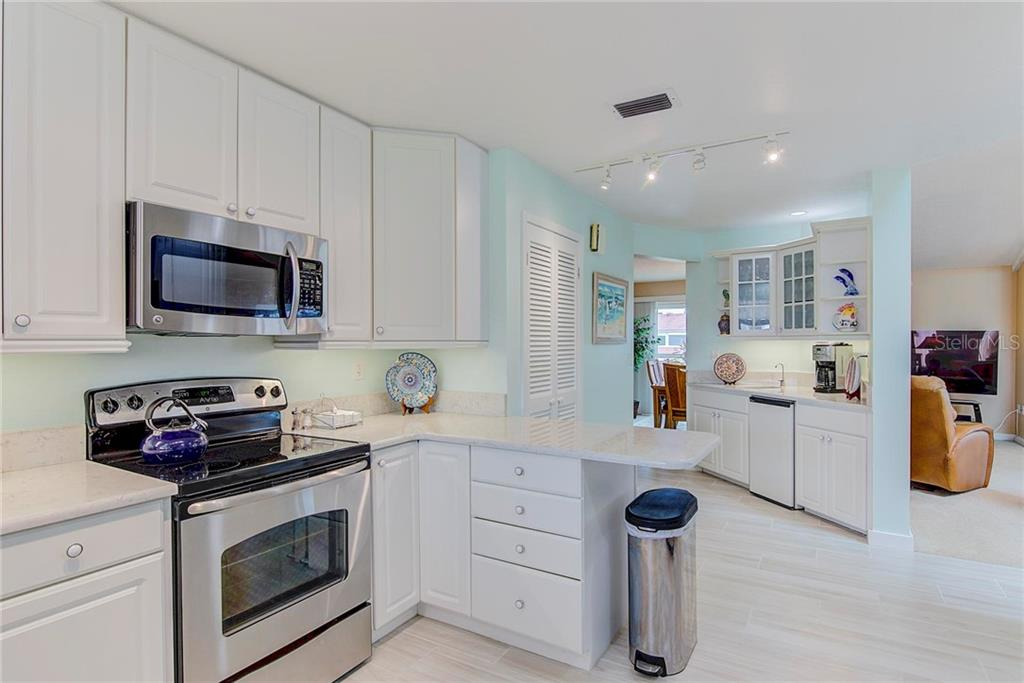 Kitchen open to dining room & living room - Condo for sale at 8750 Midnight Pass Rd #502c, Siesta Key, FL 34242 - MLS Number is A4416020