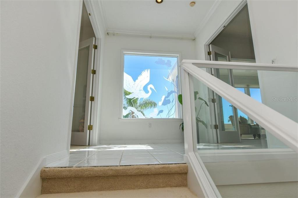 Etched glass feature to showcase views of waterfront. - Single Family Home for sale at 7689 Cove Ter, Sarasota, FL 34231 - MLS Number is A4417242