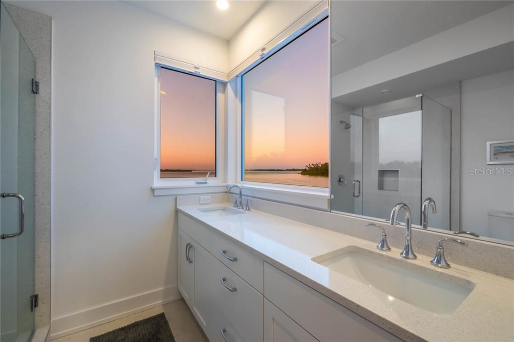 Master bath at twilight - Single Family Home for sale at 7130 Longboat Dr E, Longboat Key, FL 34228 - MLS Number is A4418105