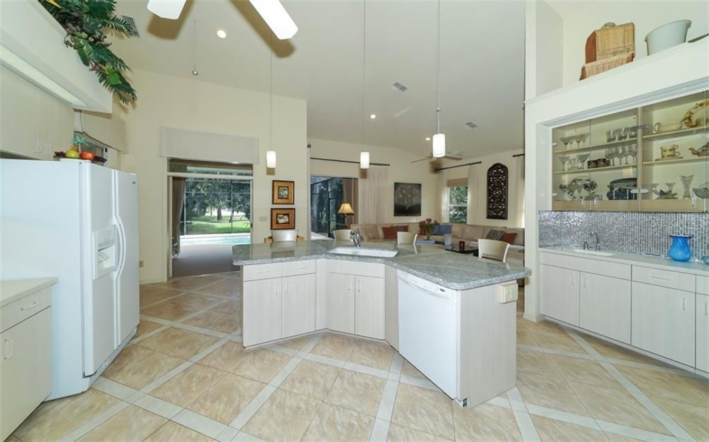 Kitchen openly flows into the large family room. French doors to lanai. - Single Family Home for sale at 6125 Varedo Ct, Sarasota, FL 34243 - MLS Number is A4420656