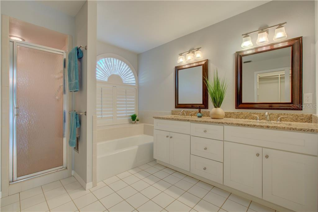 Master bathroom with dual vanities, tub and separate shower - Single Family Home for sale at 5167 Kestral Park Ln, Sarasota, FL 34231 - MLS Number is A4421162