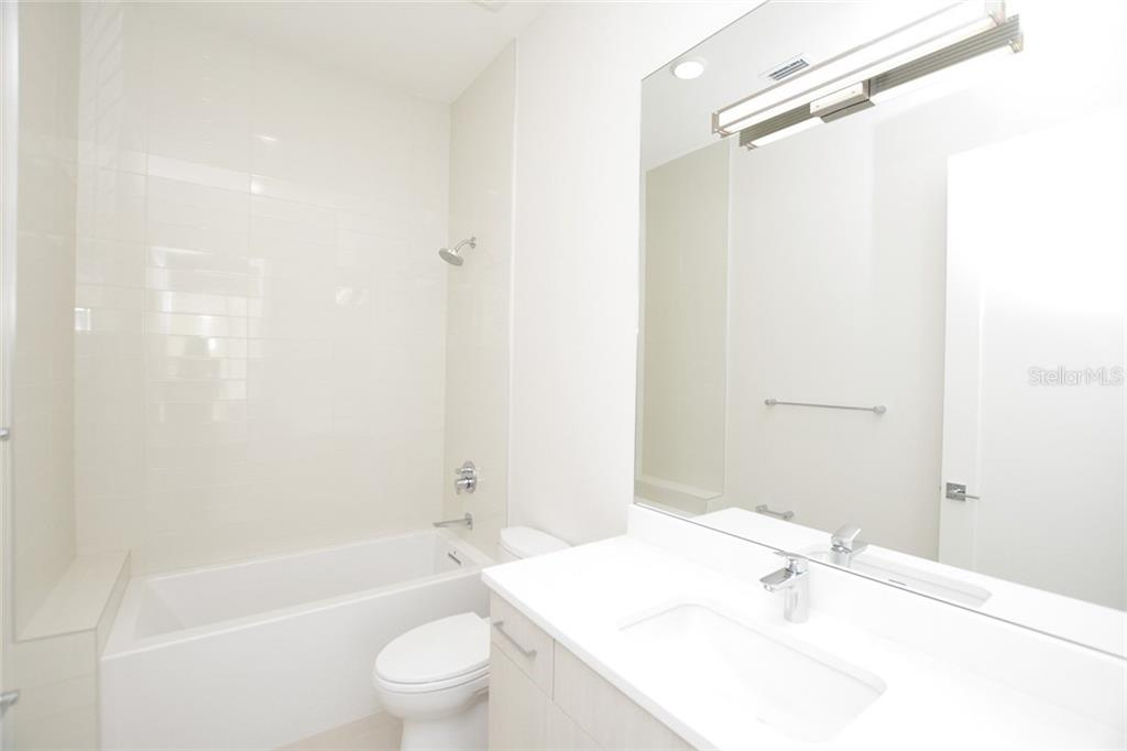 Bedroom 3 ensuite bath offers a tub/shower combination. - Condo for sale at 609 Golden Gate Pt #301, Sarasota, FL 34236 - MLS Number is A4422419