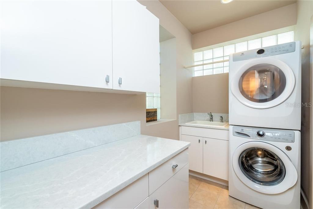 Laundry room with glass block windows for natural light, utility sink, folding space, cabinetry and pocket door access to expansive master suite closet! - Single Family Home for sale at 509 Venice Ln, Sarasota, FL 34242 - MLS Number is A4425092