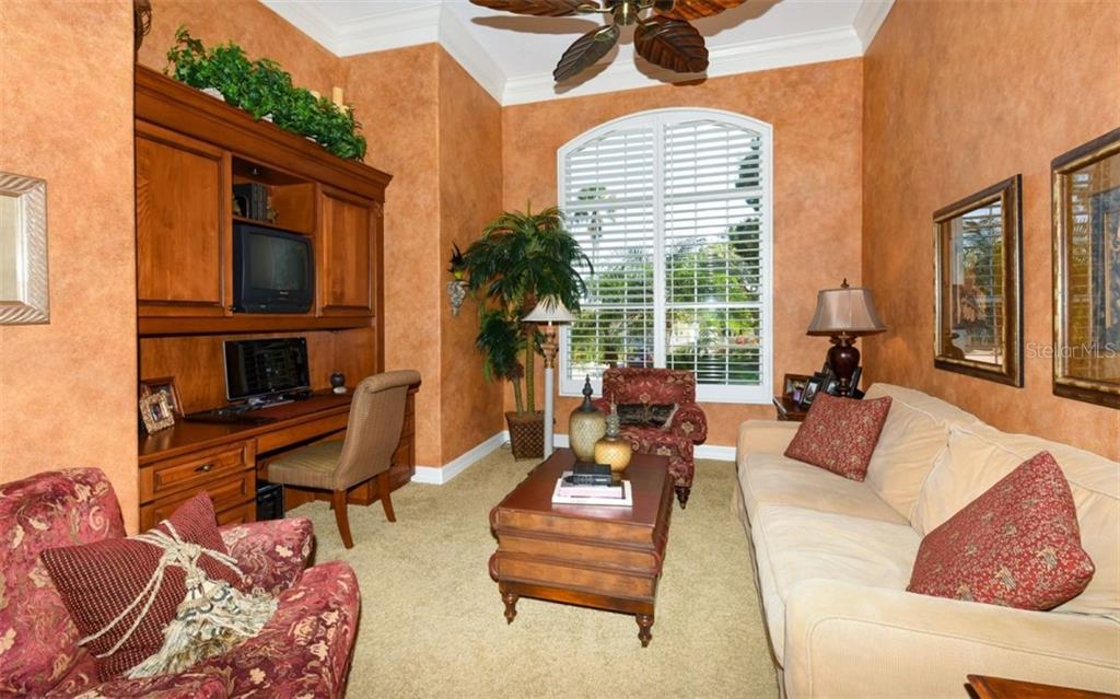 The Den which is off the living room has hand painted walls, Built in wood cabinets with desk and Plantation shutters - Single Family Home for sale at 561 Ketch Ln, Longboat Key, FL 34228 - MLS Number is A4426280
