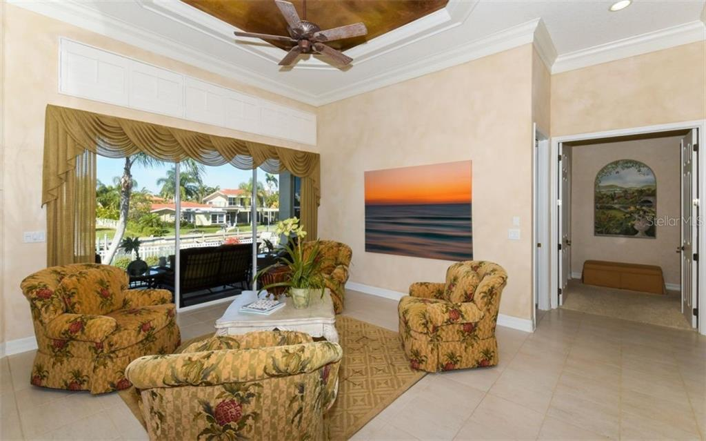 Formal Living Room with Fo painted Trey Ceiling leading to Master Bedroom through French Doors.  16 in Tile floors and a view of the pool and canal. - Single Family Home for sale at 561 Ketch Ln, Longboat Key, FL 34228 - MLS Number is A4426280