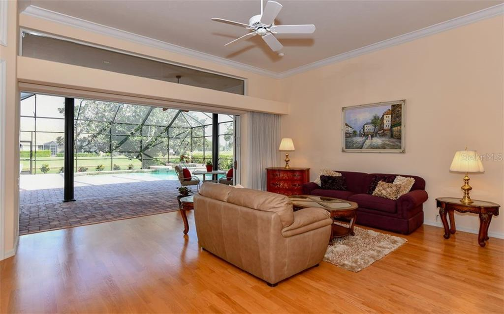 A wall of sliding glass doors separate the living room from the beautiful pool area - Single Family Home for sale at 7867 Estancia Way, Sarasota, FL 34238 - MLS Number is A4426528