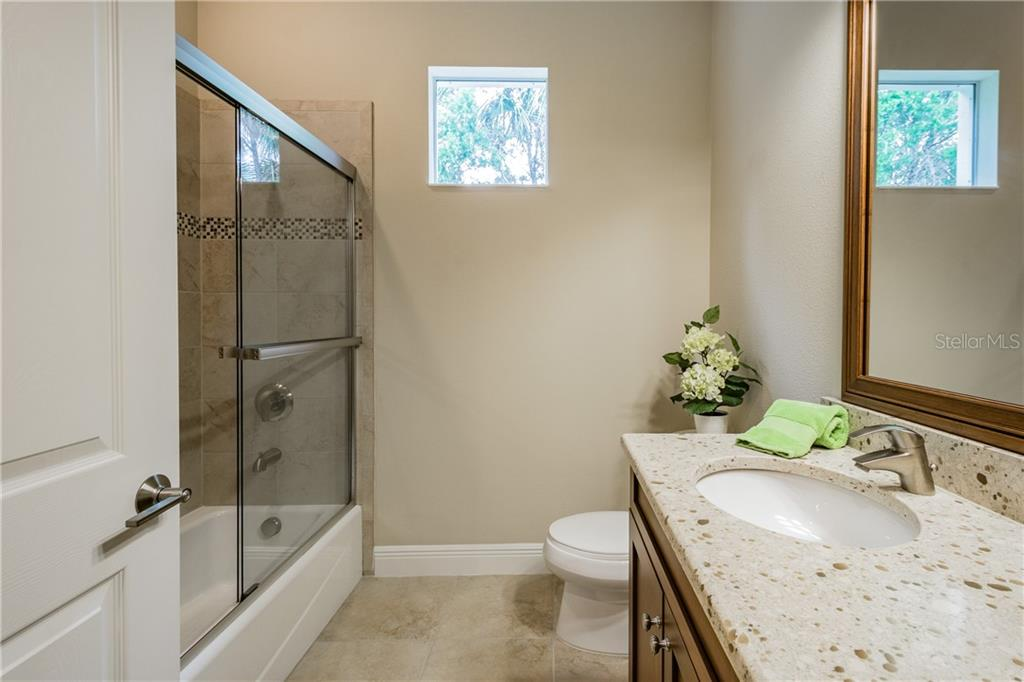 Bedroom 2 & 3 share this beautiful bath with a tub and glass enclosure - Single Family Home for sale at 595 Fore Dr, Bradenton, FL 34208 - MLS Number is A4428657