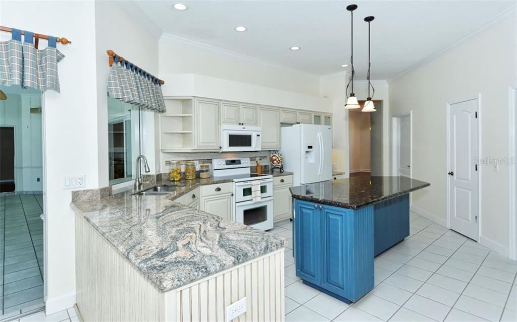 The large and airy kitchen features a large center island with breakfast bar, a pass thru window to the lanai and sliding glass door access from the eat in dining space - Single Family Home for sale at 1636 Liscourt Dr, Venice, FL 34292 - MLS Number is A4429524