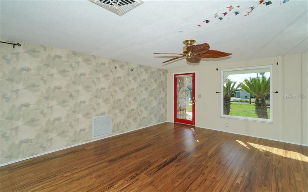 Spacious living and dining area with large picture window and gleaming wood floors. - Single Family Home for sale at 310 Bayview Pkwy, Nokomis, FL 34275 - MLS Number is A4430065